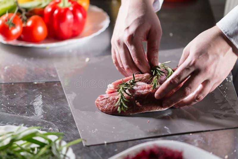 Corderos raros listos para el adobo con romero El cocinar con el fuego en sartén Cocinero profesional en una cocina de imagen de archivo libre de regalías