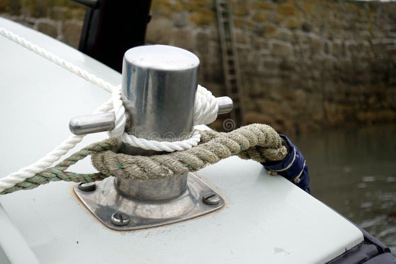 Cordes attachées autour d'un crampon ou d'une borne sur un petit bateau dans un harbou photographie stock