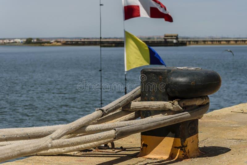 Cordes attachées dans une borne du port photographie stock