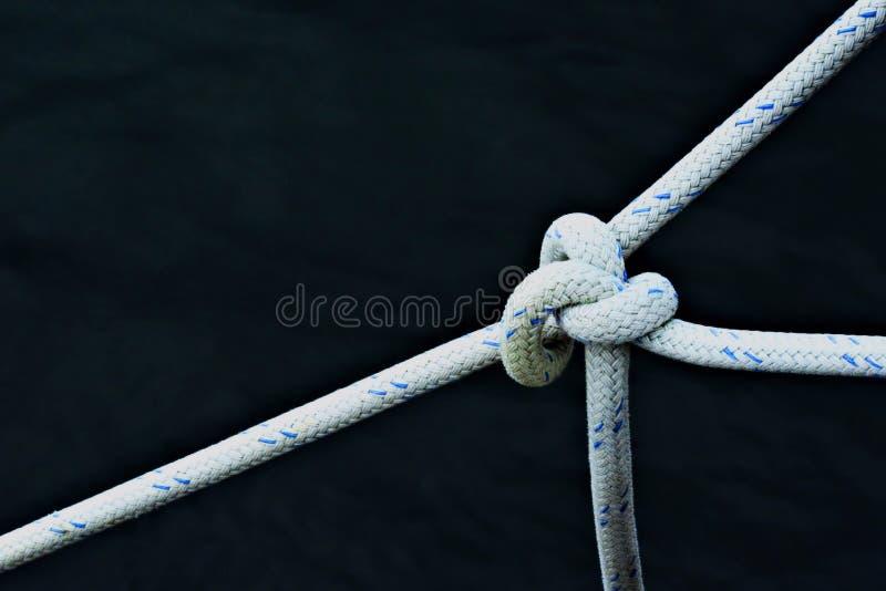 Cordes blanches attachées ensemble sur fond noir photographie stock