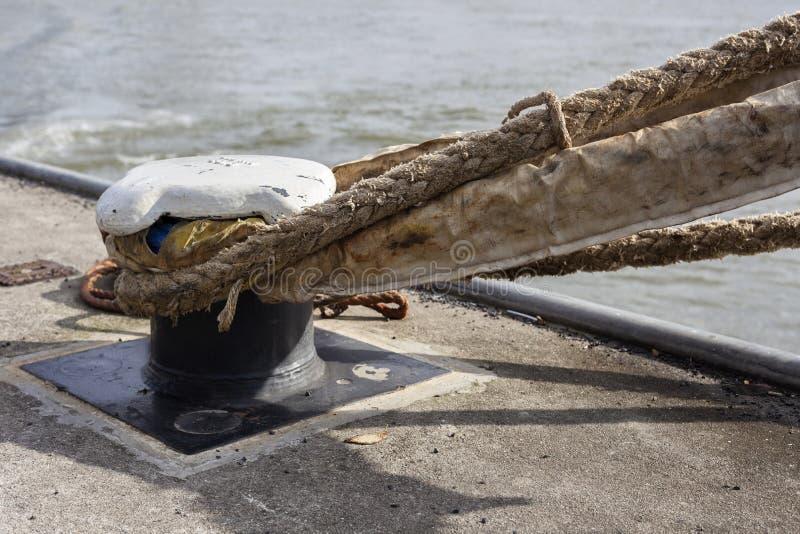 Cordes de bateau épaisses attachées à une vieille borne rouillée image stock