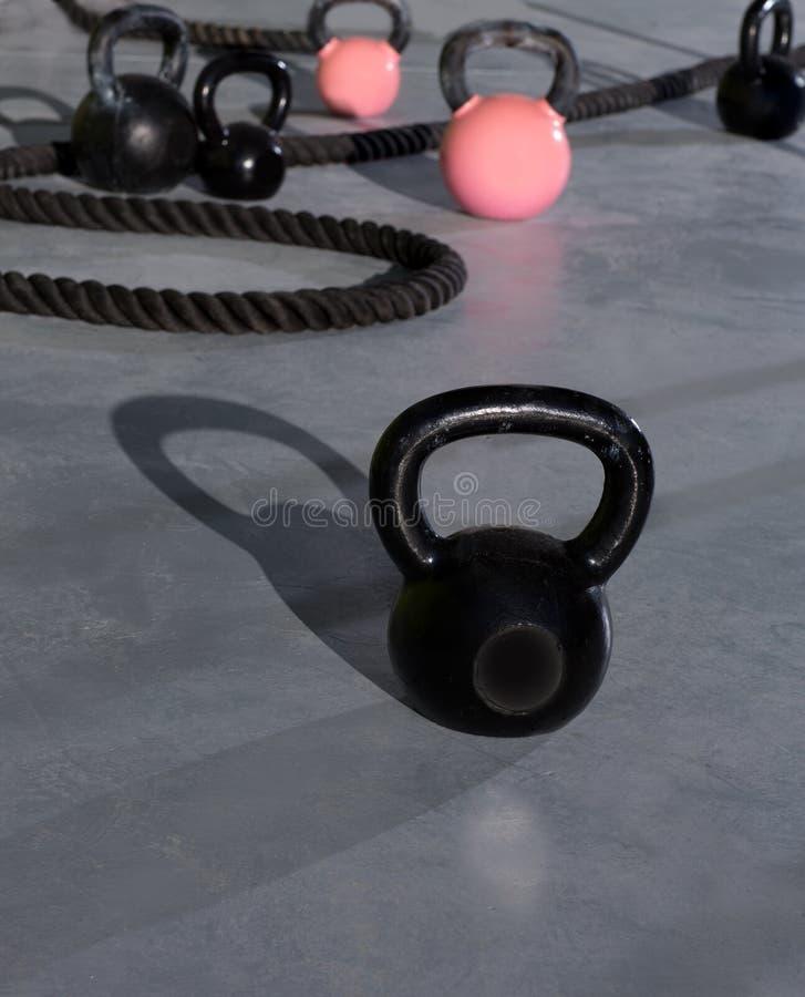 Cordes de Crossfit Kettlebells dans le gymnase de forme physique photo stock