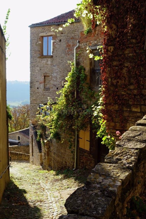 Cordes-sur-Ciel En gammal smal sten-stenlagd gränd som omges av väggar av forntida hus royaltyfri bild