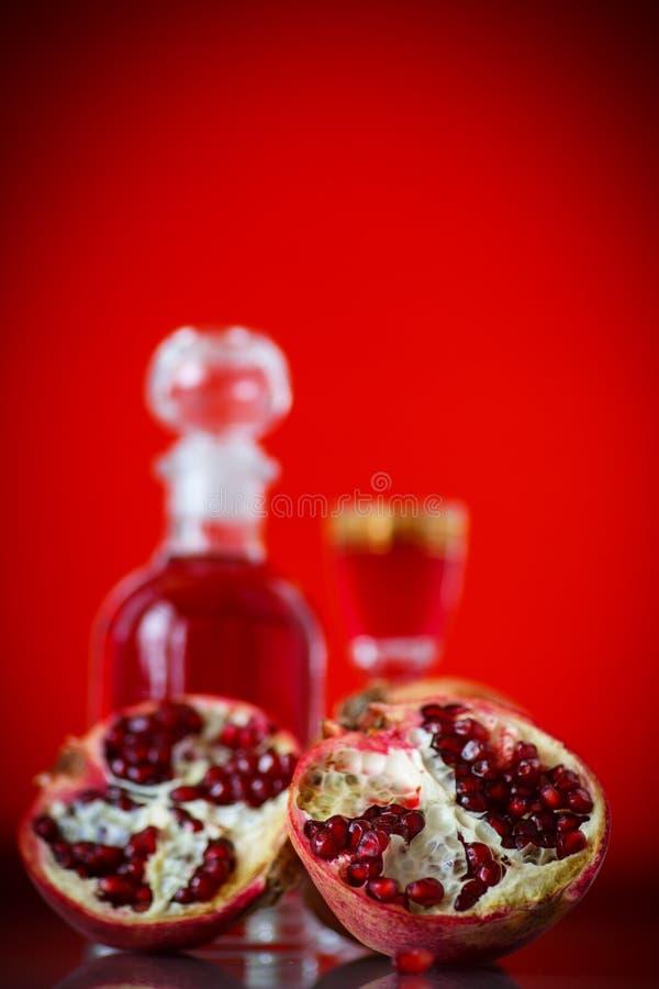 Cordial alcohólico de la granada dulce en la jarra con un vidrio foto de archivo