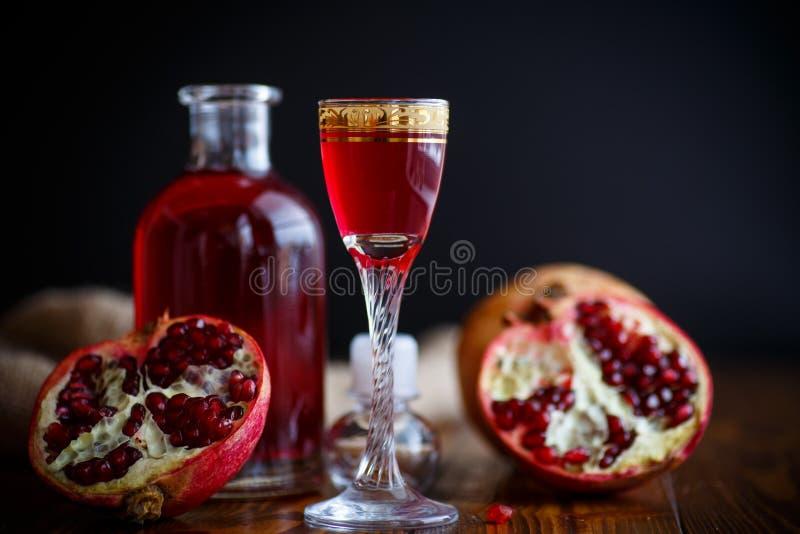 Cordial alcohólico de la granada dulce en la jarra con un vidrio foto de archivo libre de regalías