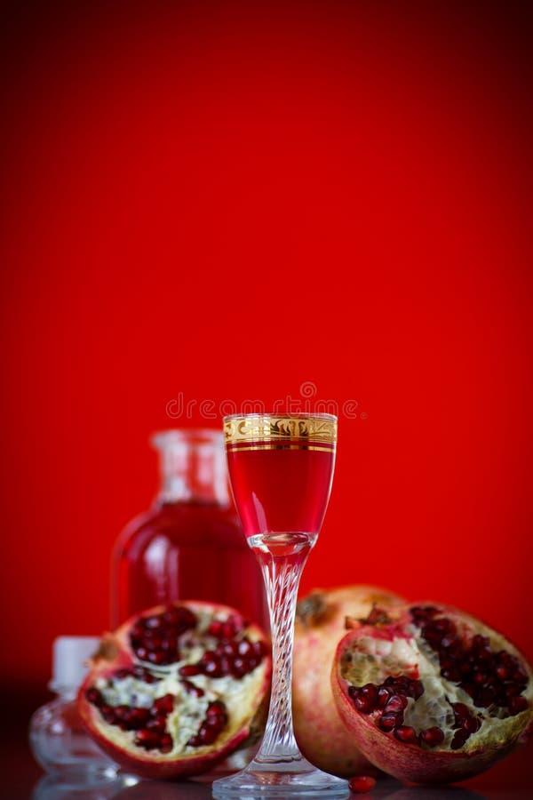 Cordial alcohólico de la granada dulce en la jarra con un vidrio fotografía de archivo libre de regalías