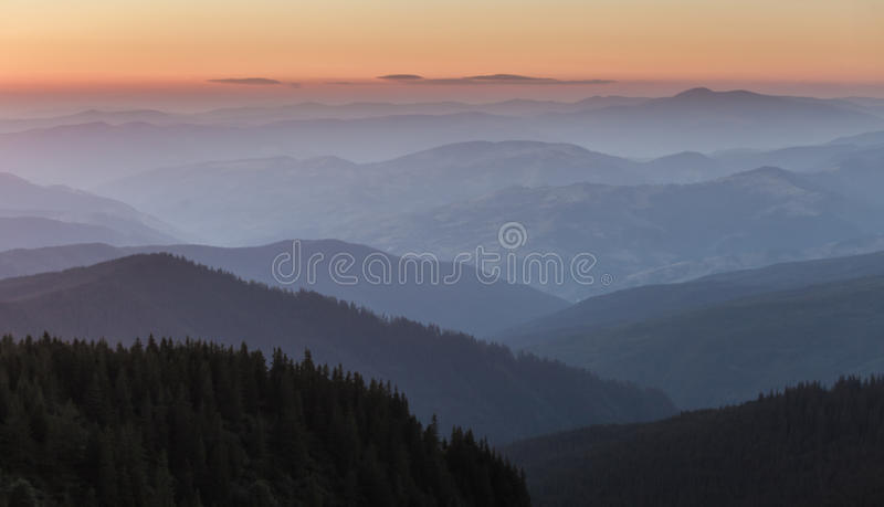 Cordilheira distante e camada fina de nuvens nos vales foto de stock