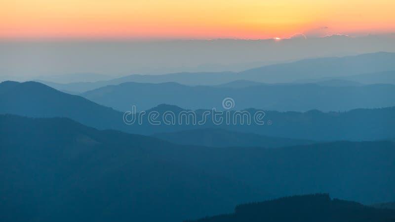 Cordilheira distante e camada fina de nuvens nos vales imagem de stock