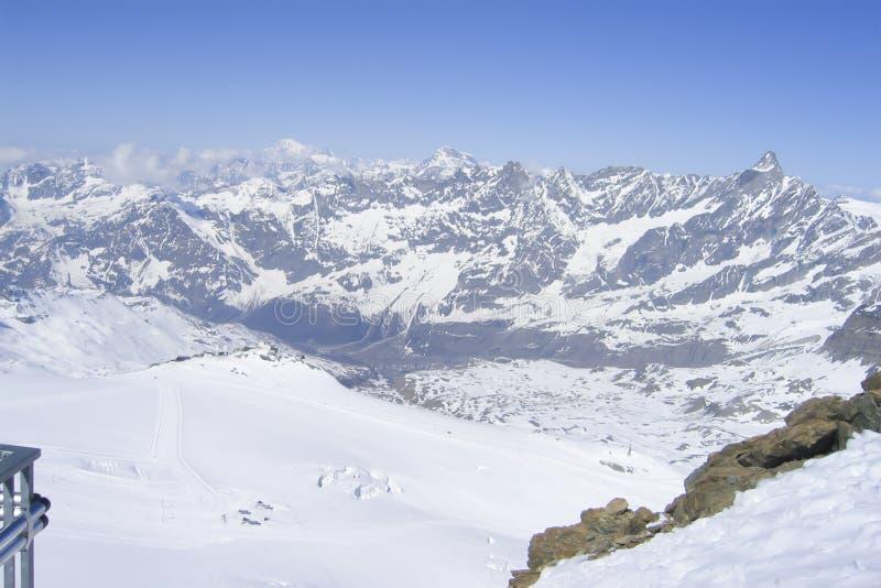 Cordilheira nevado que corre para baixo no vale em cumes suíços imagem de stock royalty free