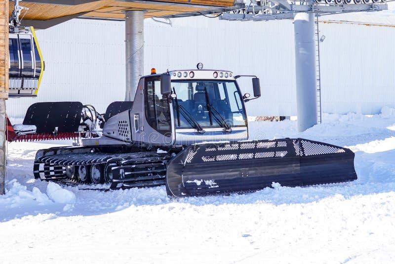 Cordilheiras empilhadeira do esqui Arado de neve do Snowblower para a snowboarding e o esqui em declive Os picos de Elbrus Cáucas imagem de stock