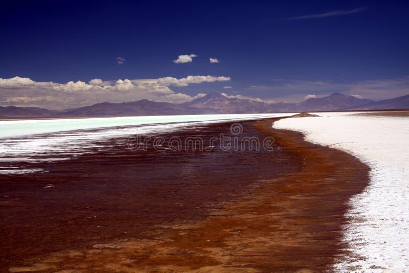 Cordillera borrosa debajo de la alfombra dramática de la nube que pone en contraste con el lago de sal brillante blanco y azul fotos de archivo libres de regalías