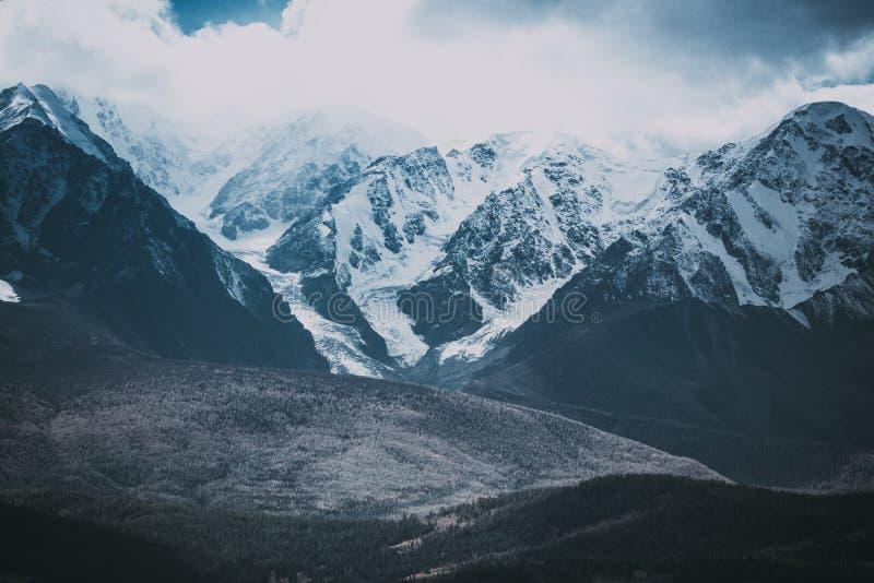 Cordillera hermosa debajo de las nubes Picos nevados de rocas imagen de archivo