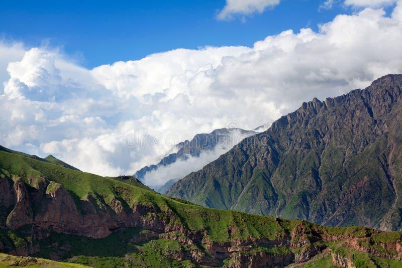 Cordilleras y montañas en el cielo azul y el primer grande blanco del fondo de las nubes, montañas caucásicas, montaña de Kazbek, fotos de archivo