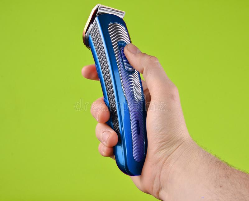Cordless clipper in a male hand isolated on a green background. stock photo