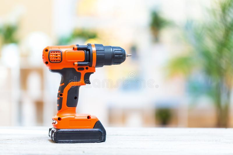 Cordless electric drill on a bright background. Cordless electric drill on a bright interior room background royalty free stock image