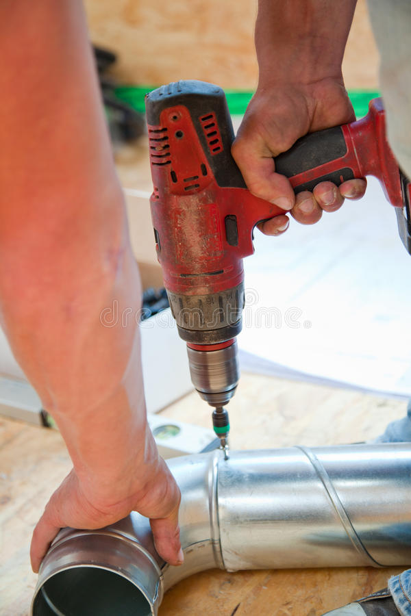 Cordless electric screwdriver. Drilling on an iron pipe with a cordless electric screwdriver stock photography