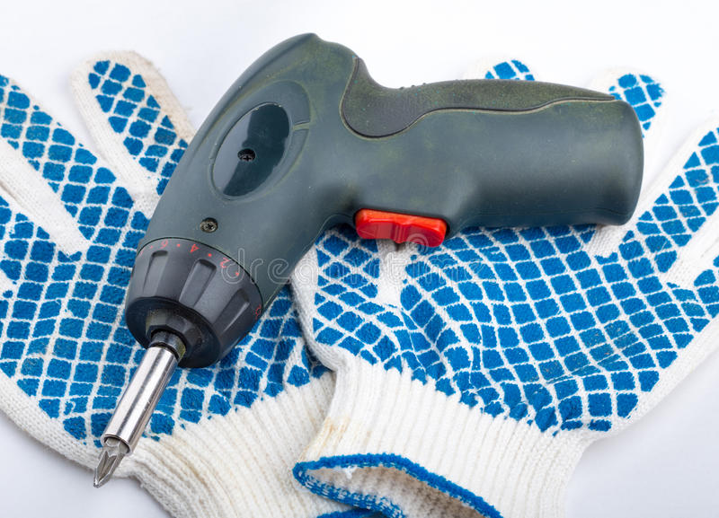 Cordless electric screwdriver and work gloves. With a pattern royalty free stock image