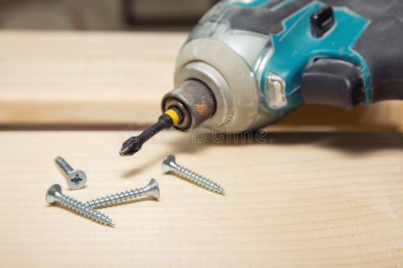 Cordless screwdriver in wooden surface with screws stock image