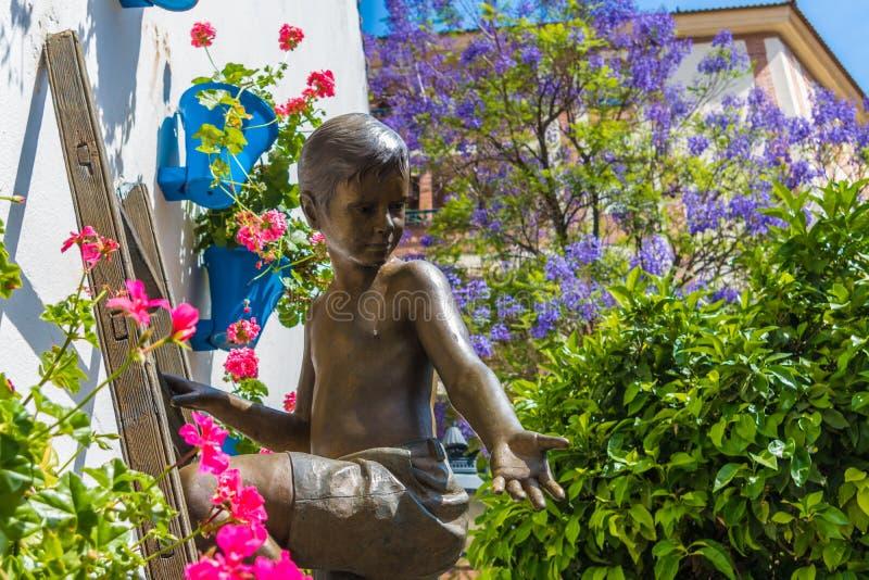 Cordoba Spanien, 08 05 2017 Skulptur av en pojke mot bakgrunden av att blomstra jacquard på den traditionella uteplatsfestivalen arkivbilder