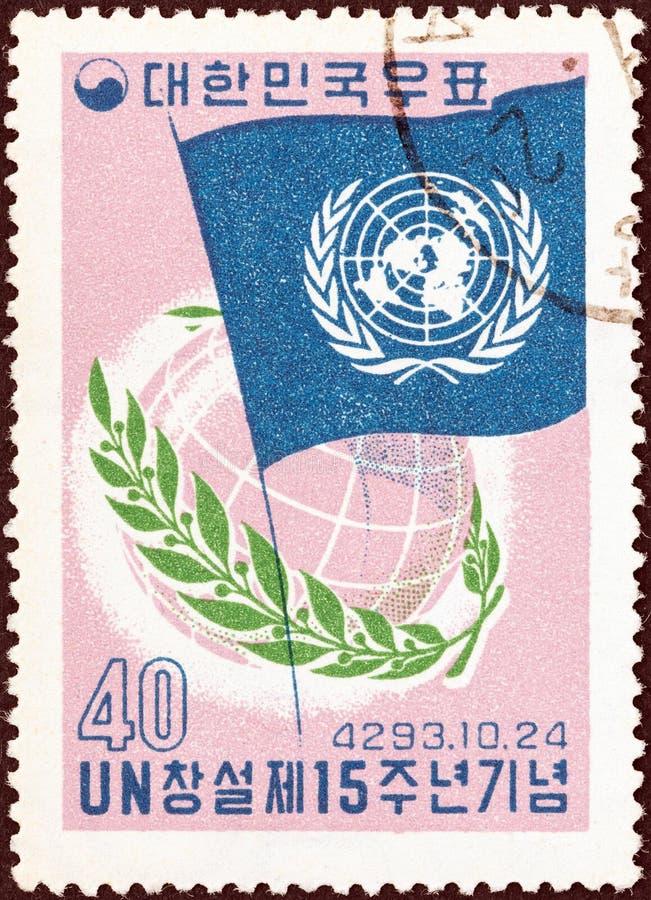 COREA DEL SUR - CIRCA 1960: Un sello impreso en Corea del Sur muestra la bandera, el globo y el laurel de la O.N.U, circa 1960 fotos de archivo