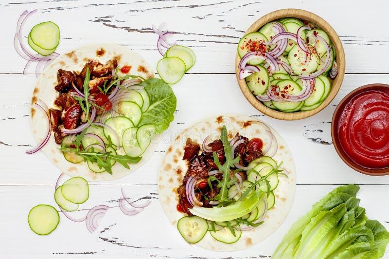 Coreano retarde tacos cozinhados da carne com slaw do pepino e ketchup asiáticos do sriracha Vista superior, configuração lisa foto de stock royalty free