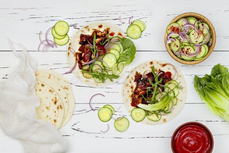 Coreano retarde tacos cozinhados da carne com slaw do pepino e ketchup asiáticos do sriracha Vista superior, configuração lisa fotos de stock royalty free