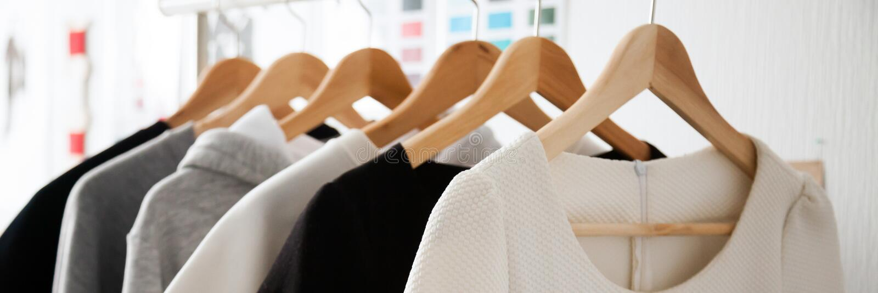 Cores brancas cinzentas brancas da escolha da roupa da forma em ganchos de madeira imagem de stock