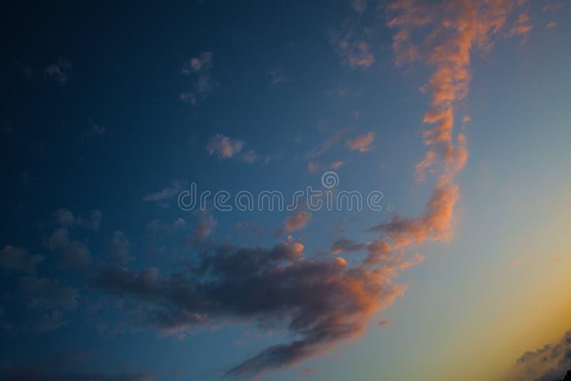 Cores brancas róseos do arrebol da tarde que iluminam o céu azul Névoa grossa que forma uma forma Partículas coloridas das nuvens foto de stock royalty free