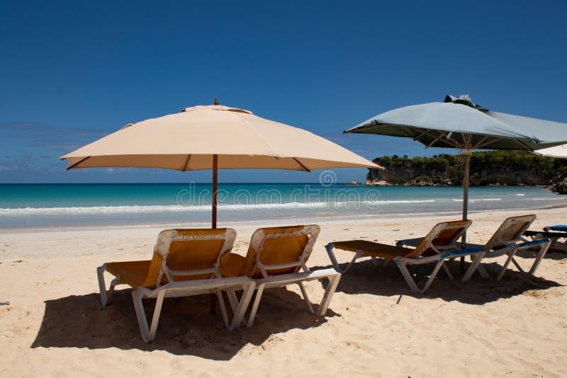 Cores das cara?bas: sunbeds e guarda-chuvas na praia p?blica, no mar azul intenso e no c?u: para?so tropical foto de stock royalty free