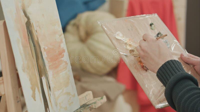 Cores de mistura do artista masculino novo na paleta e na pintura fotos de stock