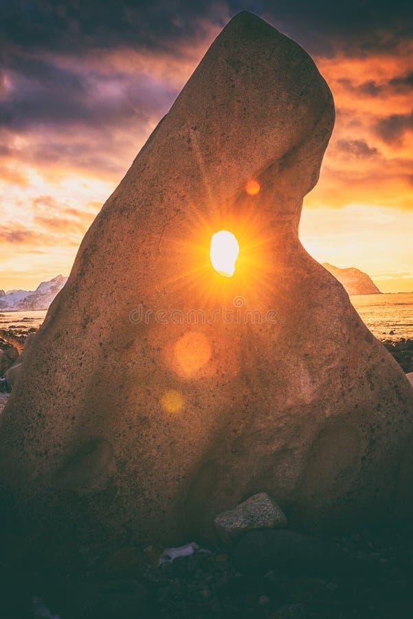 Cores de surpresa do por do sol do Atlântico Norte, paisagem do inverno com sol de brilho através de um furo na pedra estranha, c fotos de stock royalty free