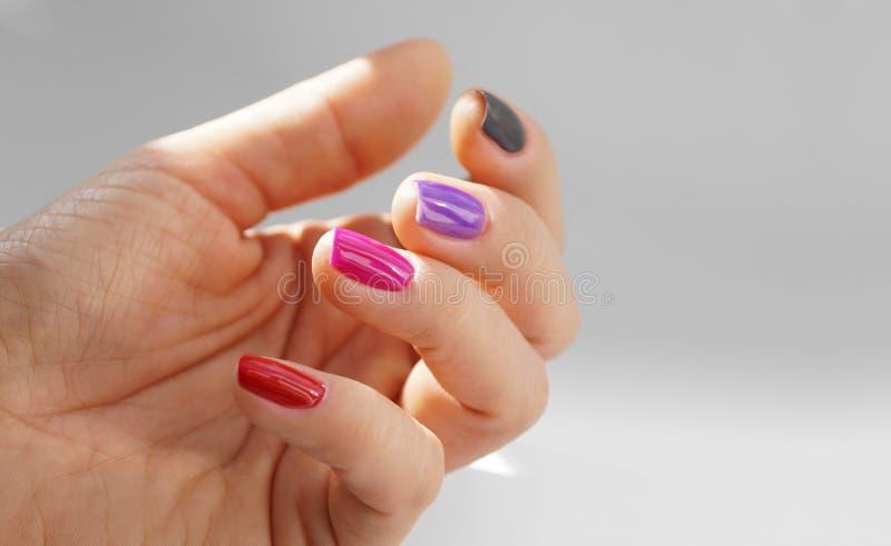 Cores diferentes do verniz para as unhas Mão feminino com pregos pintados, cada um em uma cor diferente imagens de stock royalty free