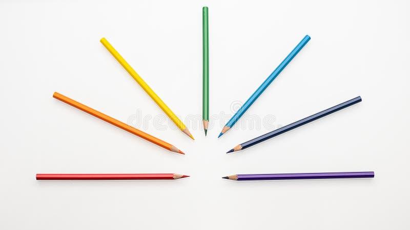 Cores do arco-íris dos lápis da cor sob a forma de um fã em um espaço branco da cópia da opinião superior do fundo fotos de stock