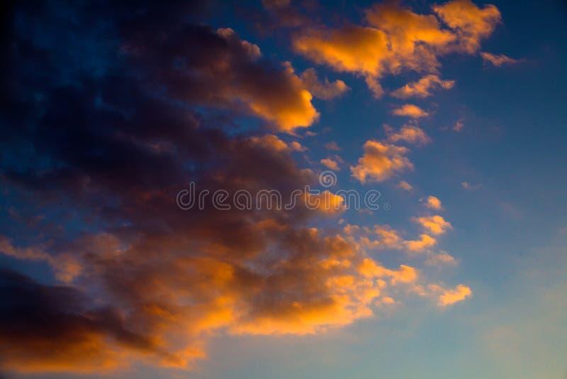 Cores do arrebol da tarde que iluminam o céu azul Nuvens cinzentas e douradas que formam uma arte finala abstrata de Cloudscape c imagens de stock