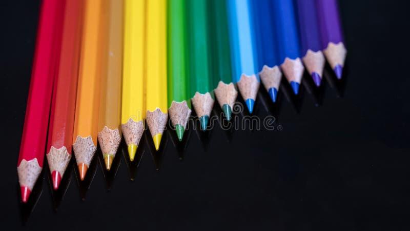 Cores do lápis do arco-íris em um vidro preto foto de stock