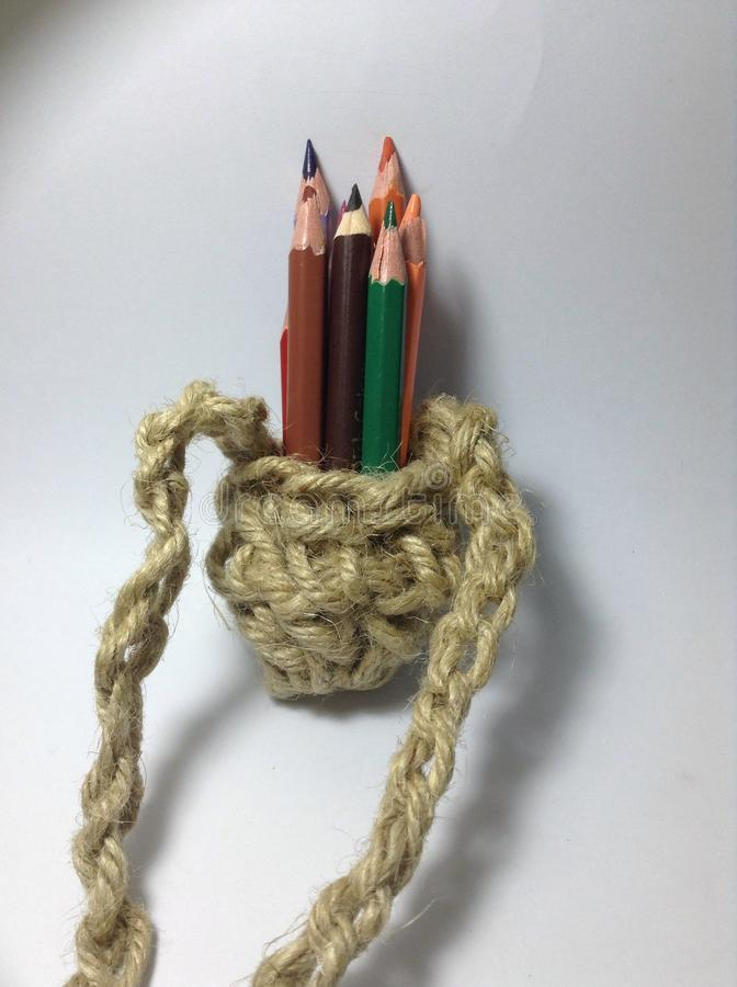 Cores do lápis em um suporte feito crochê da juta imagens de stock royalty free