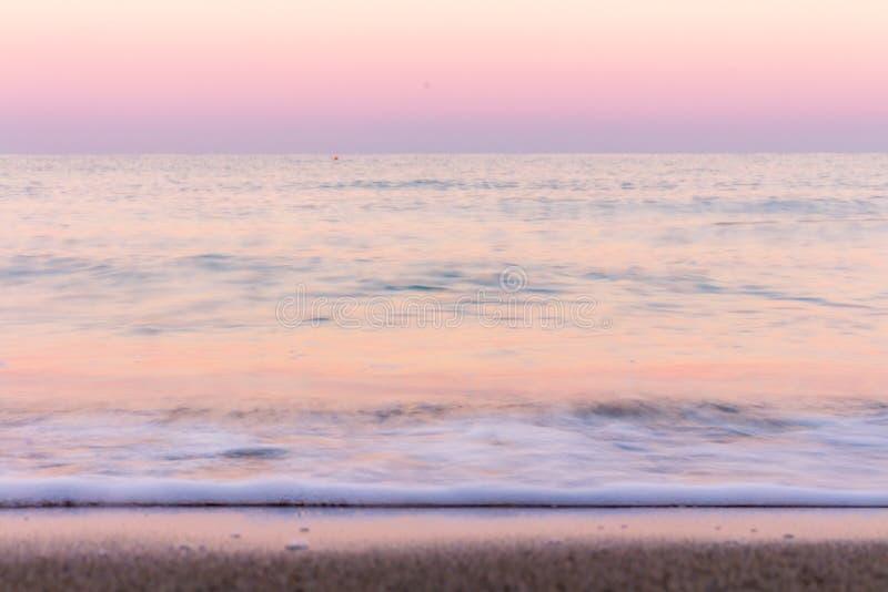 Cores do nascer do sol refletidas no borrão da água do mar imagem de stock