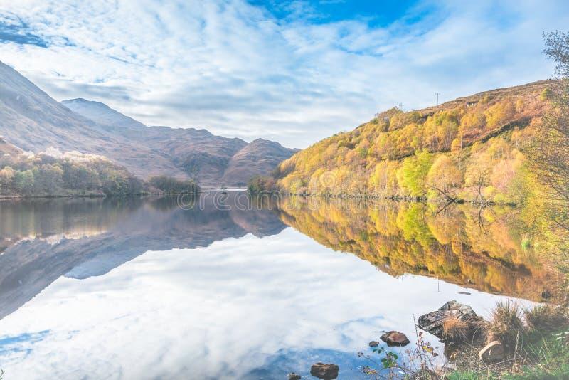 Cores do outono nas montanhas de Escócia - as árvores, montanhas, céu, montes, pedras refletiram em águas do loch foto de stock royalty free