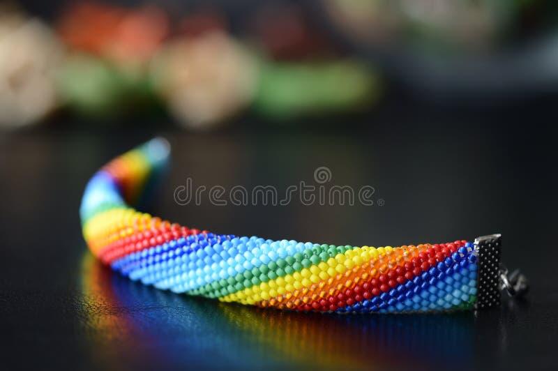 Cores feitas crochê feitos a mão do arco-íris do bracelete em um fundo escuro fotos de stock royalty free