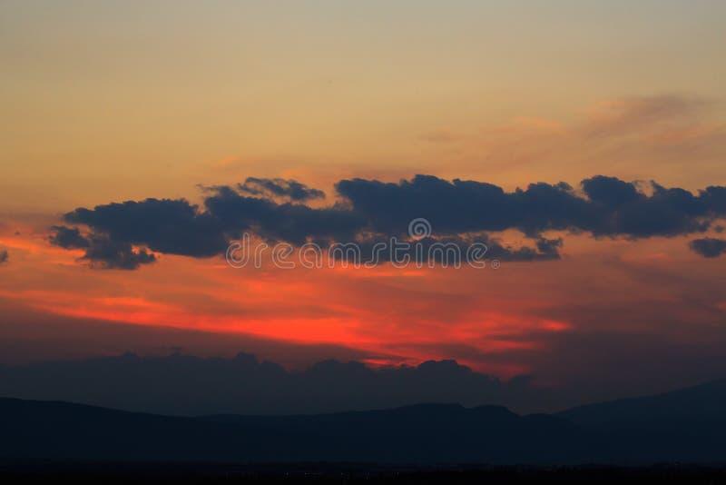 Cores impetuosas, alaranjadas e vermelhas do céu do por do sol Fundo bonito fotografia de stock