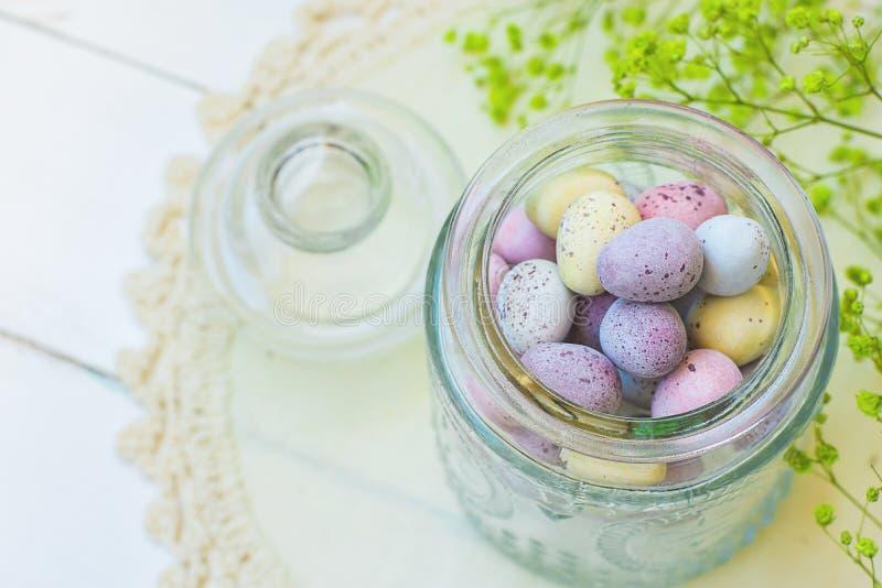 Cores pastel pequenas Multi-coloridas dos ovos da páscoa das codorniz dos doces de chocolate no frasco de vidro do vintage nas fl fotos de stock