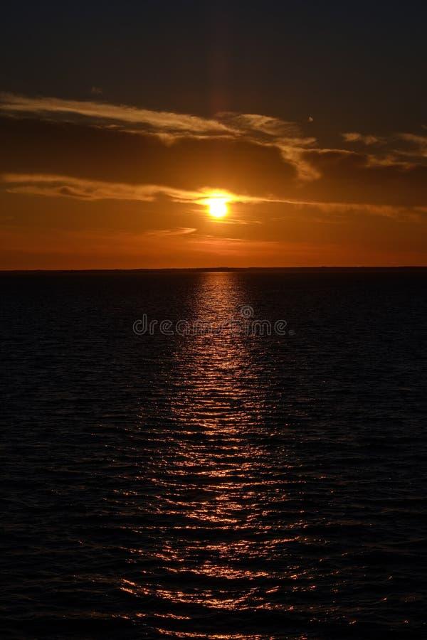 Cores saturadas vermelhas no por do sol sobre o mar Báltico com reflexões calmas da água e do sol em Estônia imagem de stock royalty free