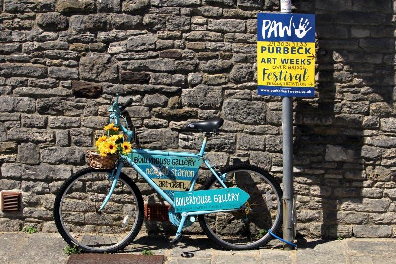 Corfe, Англия - 3-ье июня 2018: Украшенный голубой велосипед принадлежа к галерее Boilerhouse, рекламирующ неделю искусства Purbe стоковые фото