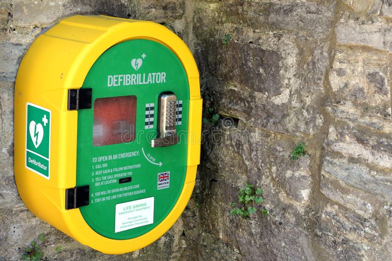Corfe, Dorset, UK - Jun 03 2018: A publicly accessible automated external defibrillator AED on a stone wall, for emergency use i. N case of someone suffering stock photography