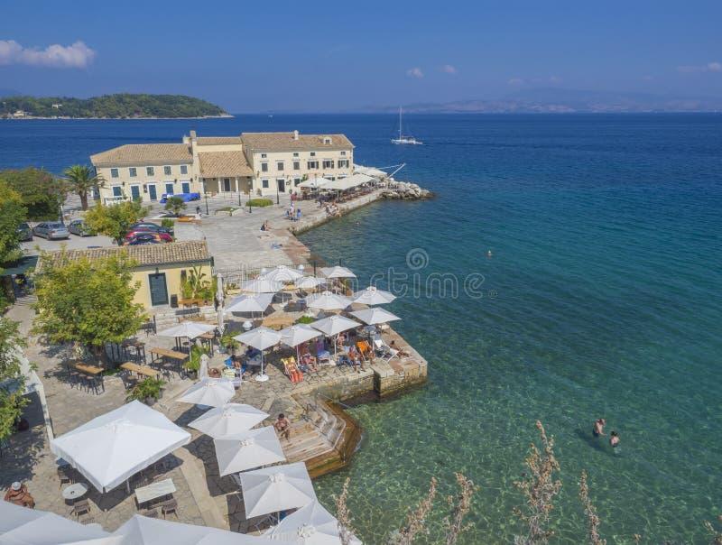 Corfou, Grèce - 7 juin 2017 : Tache se baignante publique de bains d'Alecos de plage de Faliraki avec le restaurant de l'OLP d'en photos libres de droits