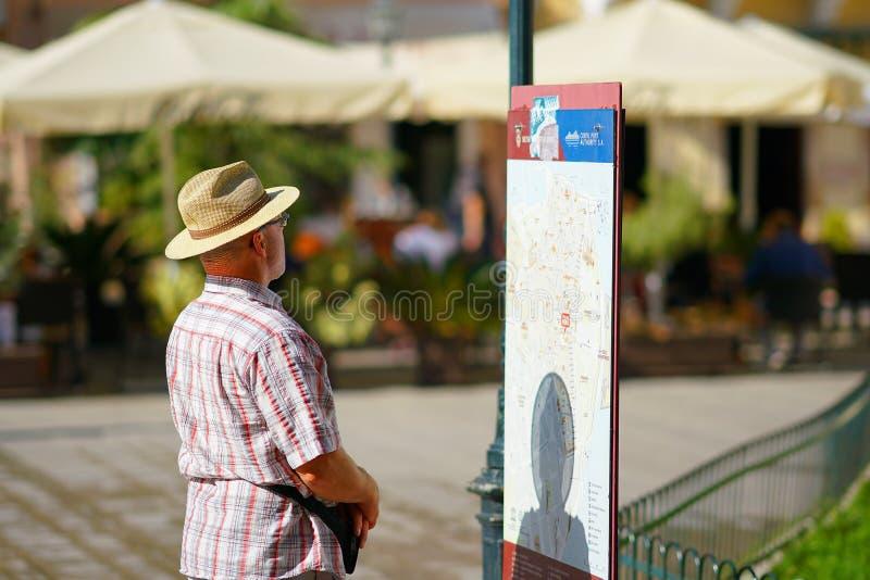 CORFOU, GRÈCE, LE 18 OCTOBRE 2018, un touriste regarde avec l'intérêt une carte de touristes dans la place de Dimarcheio images stock