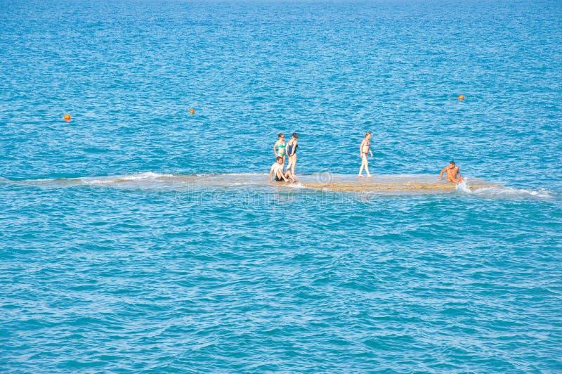 CORFU-AUGUST 26: People sunbath on an isle next to the sandy Sidary beach on August 26,2014 on the Corfu island, Greece. royalty free stock photo