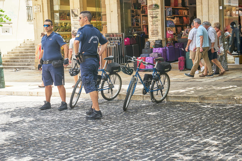 CORFU, GREECE - June 11, 2016, Police officers keeping a close a. CORFU, GREECE - June 11, 2016. Police officers keeping a close and careful eye on people on the royalty free stock image
