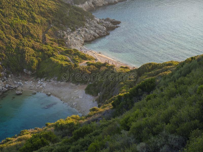 Corfu, Greece, Porto Timoni. View of the most famous double beach and bay in Afionas from the view point on the path. Sunset golde. N golden hour light royalty free stock photography