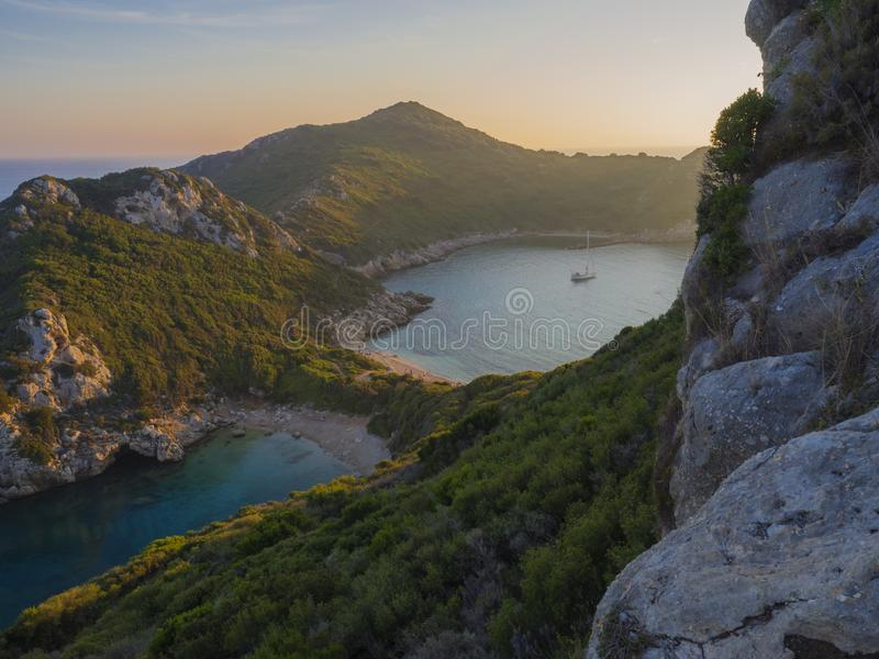 Corfu, Greece, Porto Timoni. View of the most famous double beach and bay in Afionas from the view point on the path. Sunset golde. N golden hour light stock photo